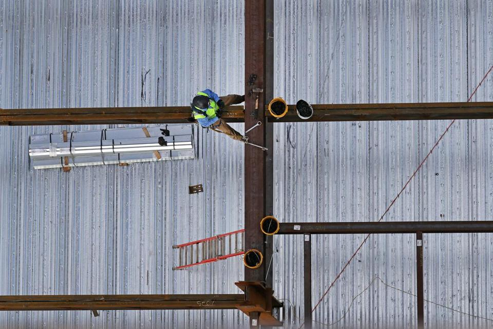 An iron worker sat on a steel beam at 121 Seaport.