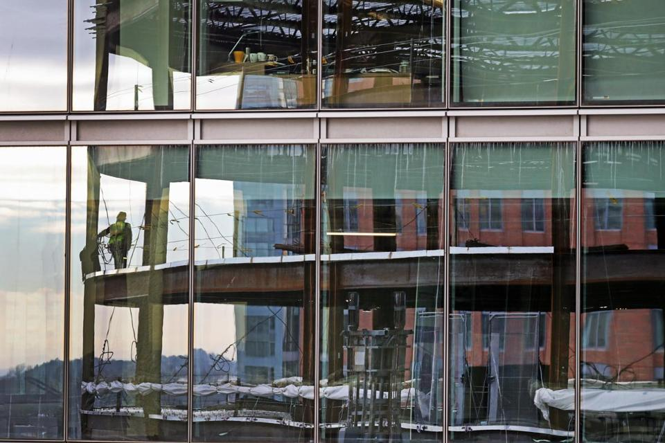 Workers on 121 Seaport, a 17-story office building being developed by Skanska USA and designed by CBT Architects, reflected in the glass walls of 101 Seaport, Skanska's recently-opened office building next door.