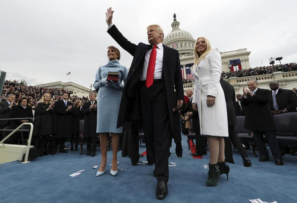 President Donald Trump waved after taking the oath of office as his wife Melania held the Bible, and Tiffany Trump looked out to the crowd.