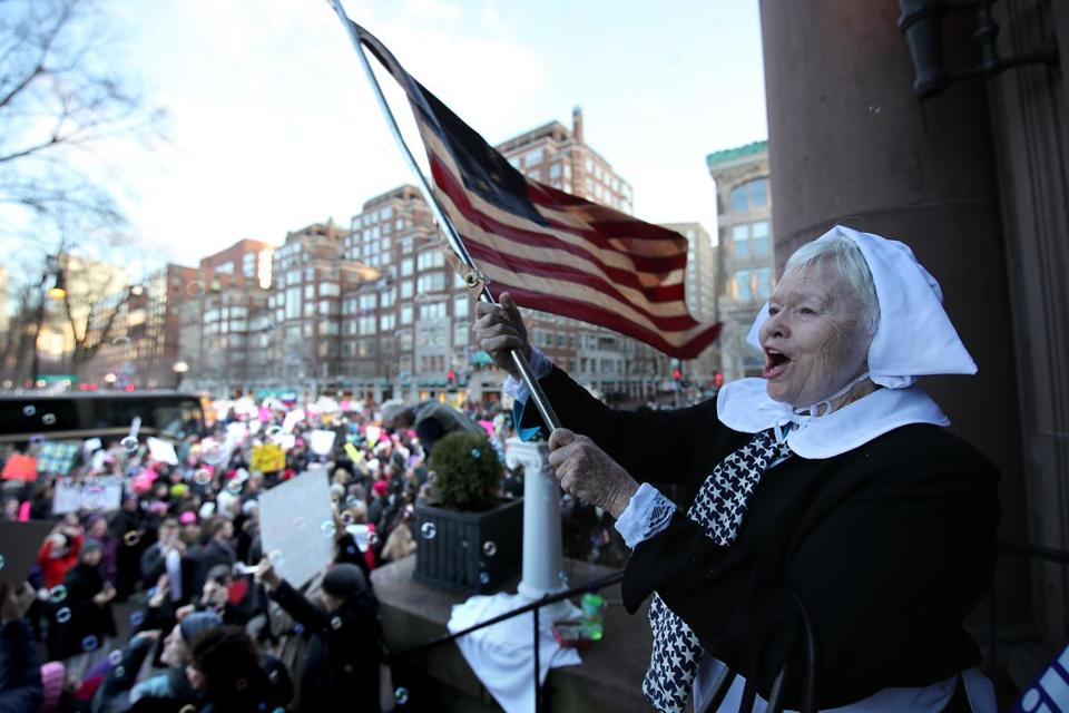 Alice Brown, who was dressed as a Mayflower-era ancestor, waved a flag on the steps of the Arlington Church.