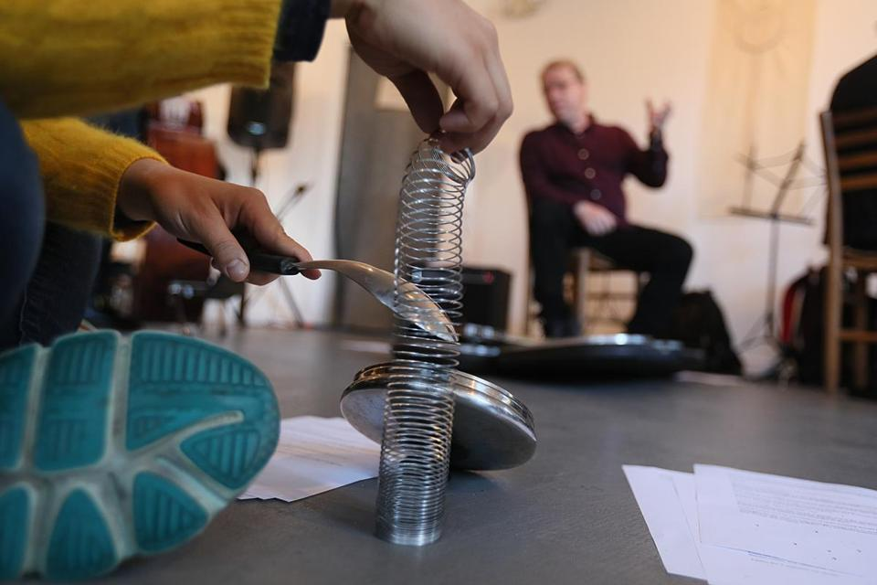 Someone makes sounds with a spoon and a slinky while composer Michael Pisaro discusses his thoughts with the group of artists.
