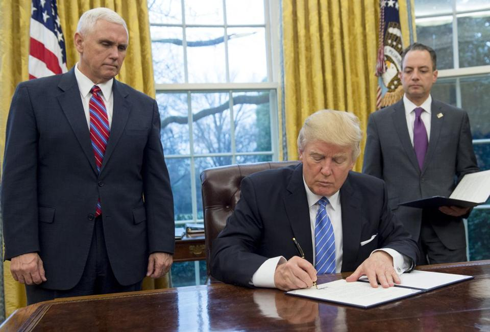 President Donald Trump signs an executive order withdrawing the United States from the Trans-Pacific Partnership alongside Vice President Mike Pence and White House Chief of Staff Reince Priebus.