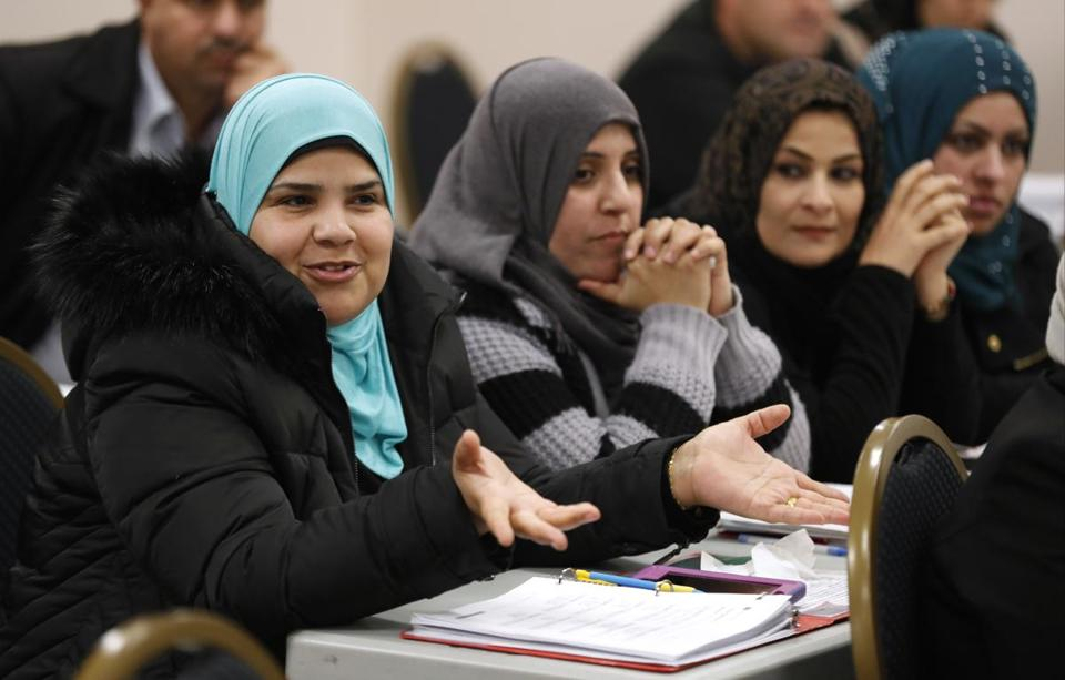 Hib Al Ogaidi (left), who moved from Baghdad, spoke during an English class in Lincoln, Neb. Ogaidi's family came to the United States on a visa after her husband worked for the US military in Iraq.