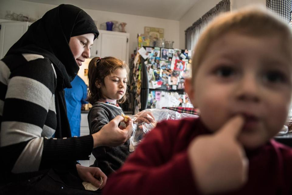 Mahasen Khatib, a Syrian refugee who is settling her family in Rutland, Vt., after months in Turkey, fed Dania, 5, one of her children.