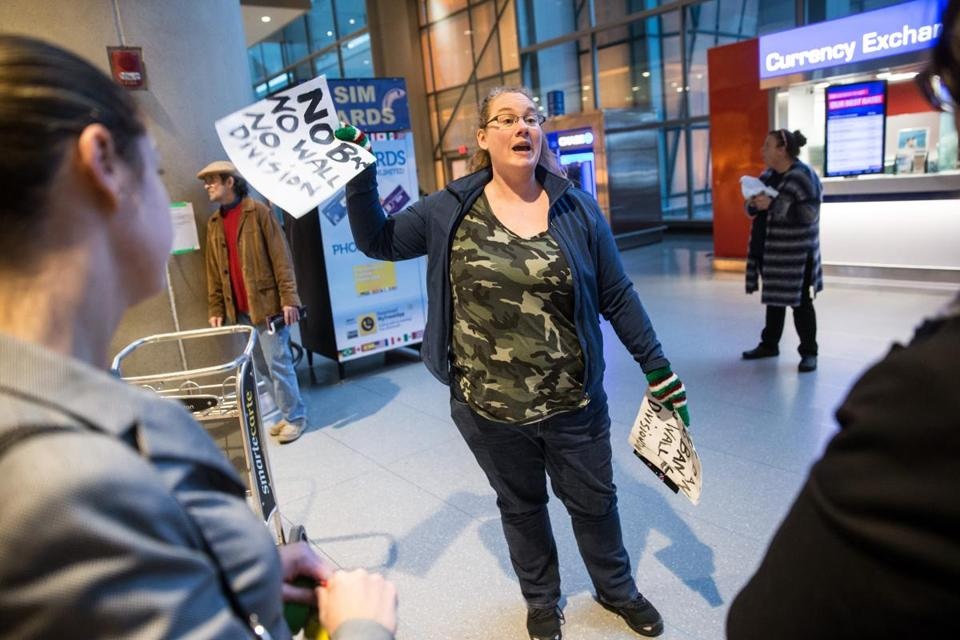 "Protester Amanda Shepard  passed out signs that read ""No Ban No Wall No Division"" at Boston Logan Airport."