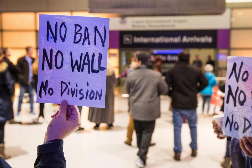 "A protester held a sign that reads ""No Ban No Wall No Division"" at Boston Logan Airport's Terminal E for international arrivals."