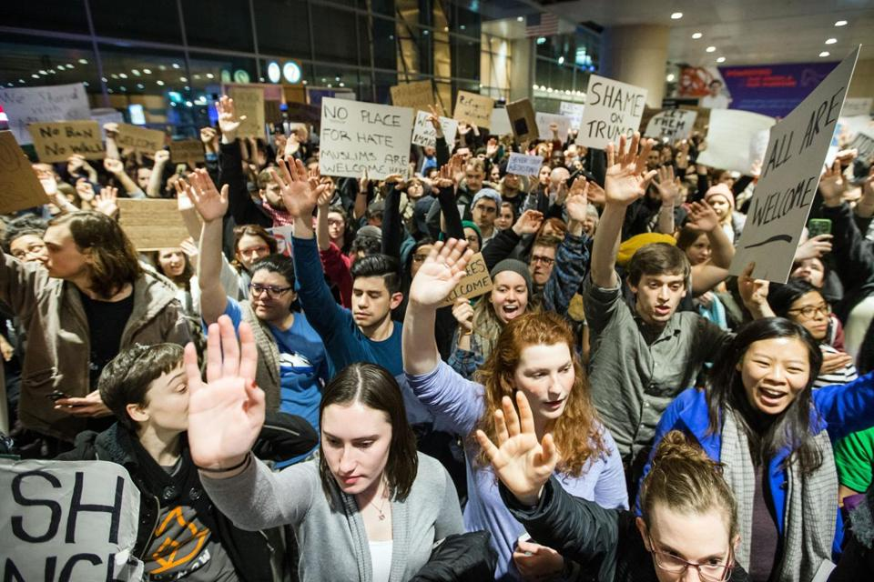 A large crowd protested the recent immigration bans at Boston Logan Airport's Terminal E for international arrivals.