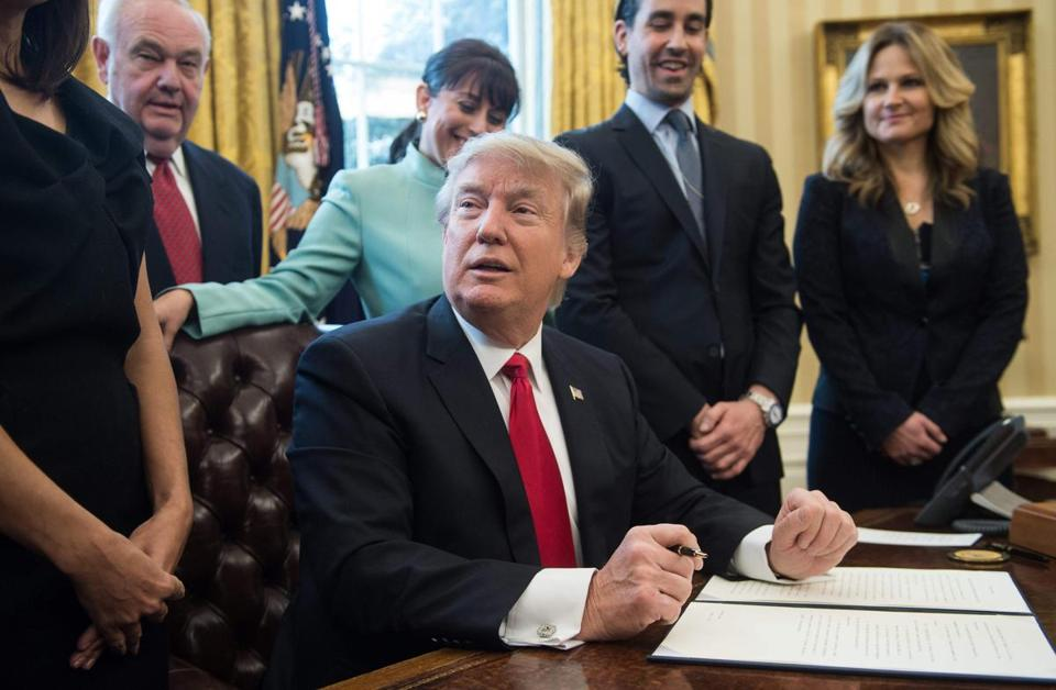 President Donald Trump was surrounded by business leaders in the Oval Office while signing the executive action Monday.