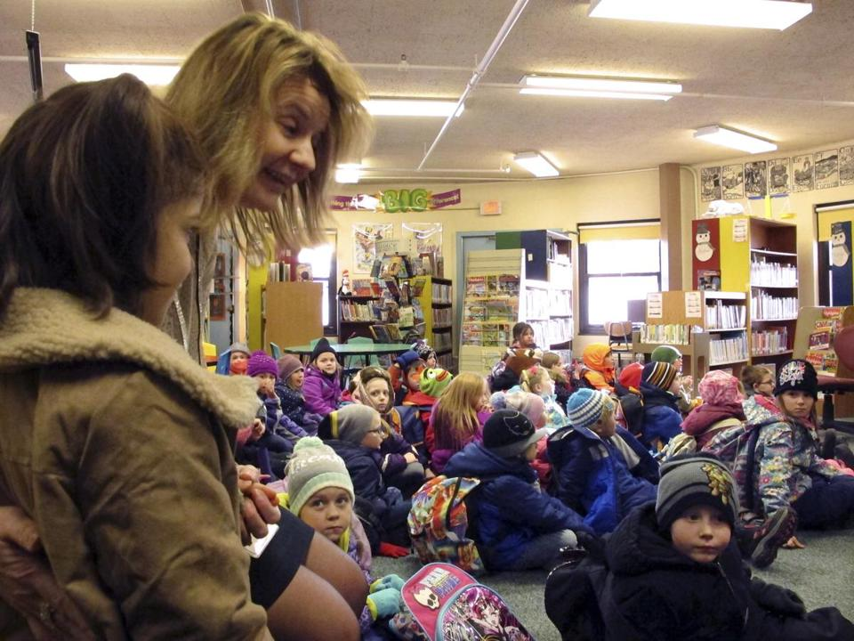 Kerry Coarse, coordinator for support services for the Northwest Primary School, introduces Dania Khatib, left, to students at the school, Friday, Jan. 27, 2017, in Rutland, Vt. Her parents fled Syria in 2012 and the family lived in Turkey until they arrived in Rutland earlier this month. (AP Photo/Lisa Rathke)