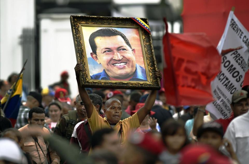 A supporter of Venezuelan President Nicolas Maduro holds a portrait of late Venezuelan President Hugo Chavez during a demonstration march to the Miraflores presidential palace in Caracas on April 7, 2016. Supporters of Venezuelan President Nicolas Maduro mobilized to ask him to block an amnesty law promoted by the opposition, and already approved in the opposition-controlled Parliament, but that still requires presidential approval. / AFP / JUAN BARRETO / JUAN BARRETO (Photo credit should read JUAN BARRETO/AFP/Getty Images)