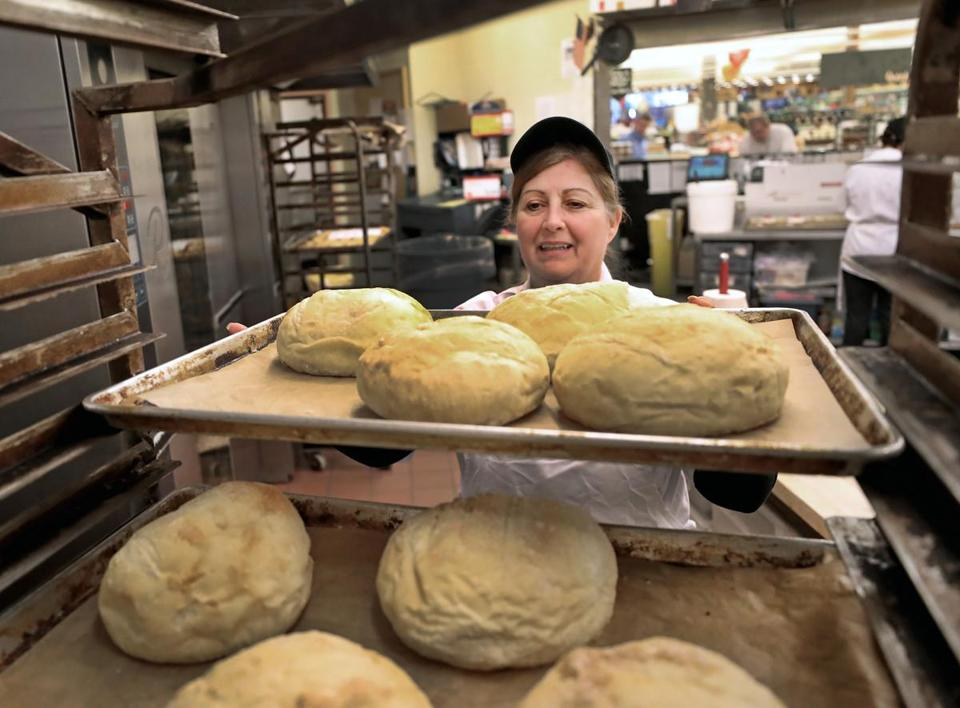 Bakery manager Cathy Curry loaded bread on to trays while working at the Roche Bros. store in Quincy.