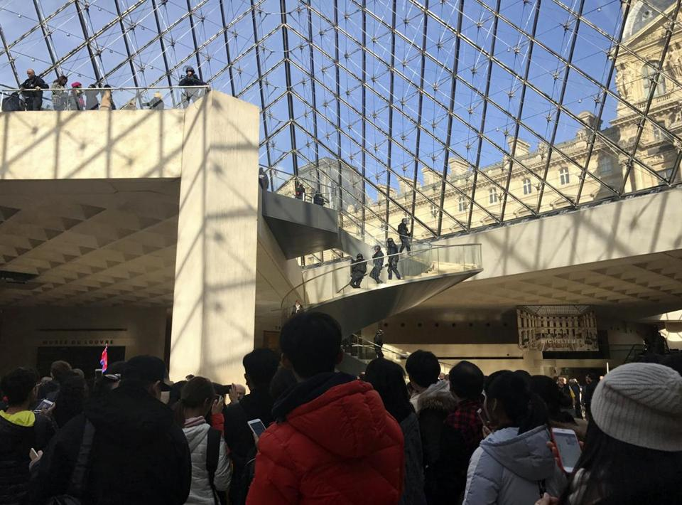 Tourists were led from the Louvre in Paris on Friday after a man with a machete lunged toward soldiers in the vicinity of the world-famous museum.