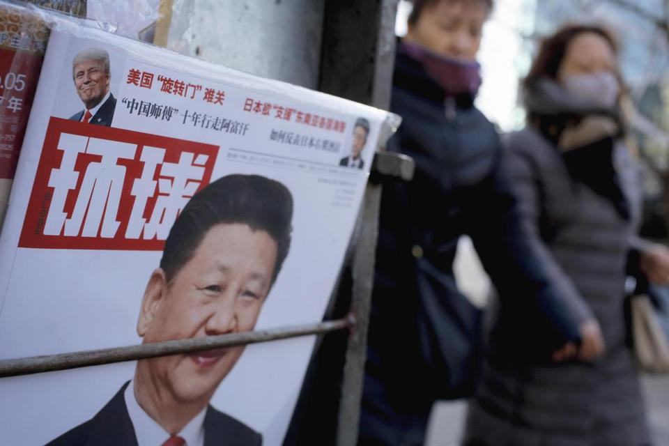 Women walked past a newsstand displaying a Chinese magazine fronting a photo of Chinese President Xi Jinping and US President Donald Trump in Beijing on Thursday.