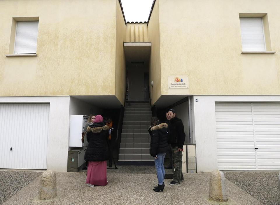 "People stand in front of the entrance of an apartment building in Clapiers, southern France, where suspects believed to be involved in ploting an attack were arrested by a French anti-terrorist police unit, Friday, Feb. 10, 2017. Anti-terrorism forces arrested four people Friday in southern France, including a 16-year-old girl, and uncovered a makeshift laboratory with the explosive TATP and other ingredients for fabricating a bomb. France's top security official said the raid thwarted an ""imminent attack."" (AP Photo/Claude Paris)"