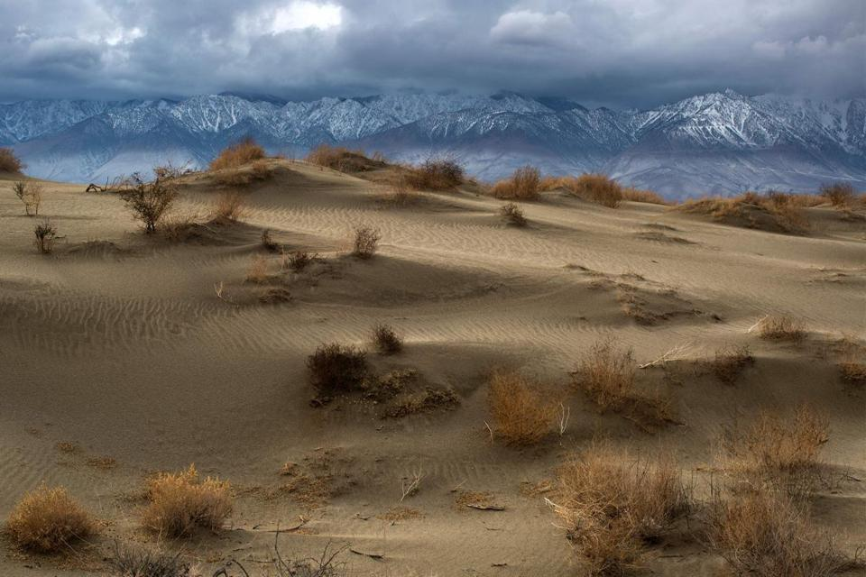 "(FILES) This file photo taken on January 08, 2017 shows Desert sand dunes are seen with snowy Eastern Sierra Nevada Mountains in the distance near Lone Pine, California. As the planet warms due to climate change and hot days become more common, the US electrical grid could be unable to meet peak energy needs by century's end, researchers warned on February 6, 2017. The cost to upgrade the US electrical grid so it could cope with peak demands may be on the order of $180 billion, said the report in the Proceedings of the National Academy of Sciences.""As the electricity grid is built to endure maximum load, our findings have significant implications for the construction of costly peak generating capacity,"" said the study. / AFP PHOTO / DAVID MCNEWDAVID MCNEW/AFP/Getty Images"