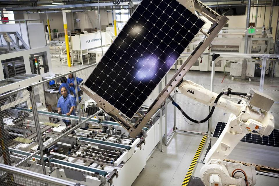 A robot stacks solar panels at Flextronics, a solar-panel factory, in Milpitas, Calif., July 10, 2012. Robots far more adept than those now commonly used by automakers and other industries are replacing workers in both manufacturing and distribution. (Lianne Milton/The New York Times)