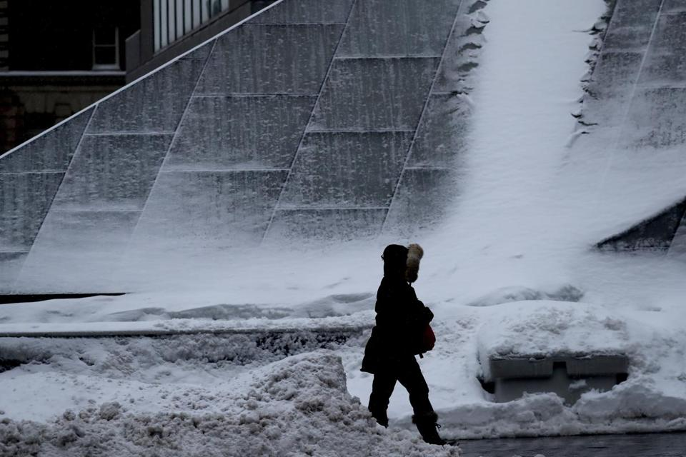 A person walks past a T station covered in snow on Summer Street on Monday morning.