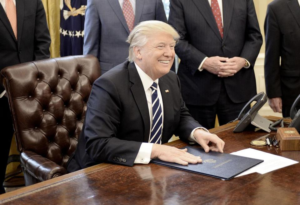 "WASHINGTON, D.C. - FEBRUARY 14: (AFP-OUT) U.S. President Donald Trump smiles after signing H.J. Res. 41 in the Oval Office of the White House on February 14, 2017 in Washington, DC. The resolution nullifies a rule in the Dodd-Frank Act that ""requires resource extraction issuers to disclose payments made to governments for the commercial development of oil, natural gas, or minerals."" (Photo by Olivier Douliery-Pool/Getty Images)"