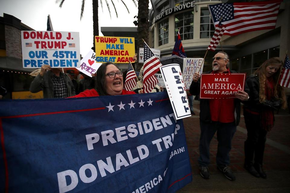 "BREA, CA - FEBRUARY 27: Supporters of U.S. President Donald Trump hold signs during a rally in favor of the ""America First"" agenda on February 27, 2017 in Brea, California. Dozens of supporters of U.S. President Donald Trump held a rally outside the office of U.S. Rep. Ed Royce (R-CA) in support of the ""America First"" agenda that the Trump administration is pushing forward. (Photo by Justin Sullivan/Getty Images)"