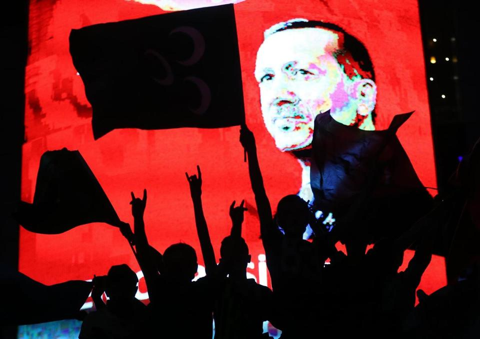 "TOPSHOT - Supporters stands in front of a screen displaying a portrait of Turkish President Recep Tayyip Erdogan during a rally at Kizilay Square in Ankara on July 20, 2016, Erdogan on Wednesday declared a three-month state of emergency, vowing to hunt down the ""terrorist"" group behind last week's bloody coup attempt. / AFP / ADEM ALTAN (Photo credit should read ADEM ALTAN/AFP/Getty Images)"