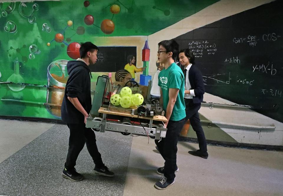 BOSTON, MA - 3/02/2017: Students walking in front of a science mural from the John D. O'Bryant School for Mathematics and Science. Students L-R Hoang Nguyen, Matthew Wang and McCain Boonma (cq) members of the schools robot club carry their robot to the auditorium for a deomostrtion where the Massachusetts Life Sciences Center was celebrating its allocation of $1.8 million in life sciences capital investments and education for 15 middle and high schools around Greater Boston, including six Boston public schools which included O'Bryant. (David L Ryan/Globe Staff Photo) SECTION: METRO TOPIC 03lifesciences