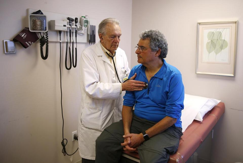 Dr. William Cobb (left) listened to Dr. Roger Kligler's heart during an appointment.