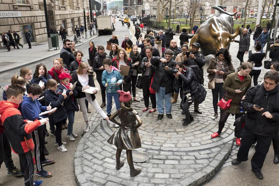 "A crowd gathers around a statue of a fearless girl facing the Wall Street Bull, Wednesday, March 8, 2017, in New York. The statue was installed by an investment firm in honor of International Women's Day. An inscription at the base reads, ""Know the power of women in leadership. She makes a difference. State Street Global Advisors."" (AP Photo/Mark Lennihan)"