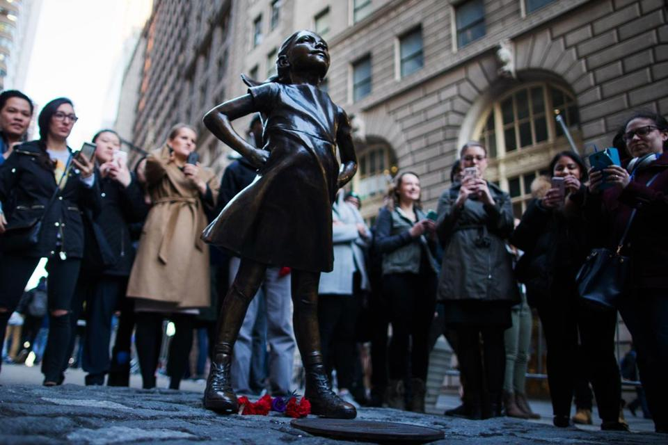People look at 'The Fearless Girl' statue.