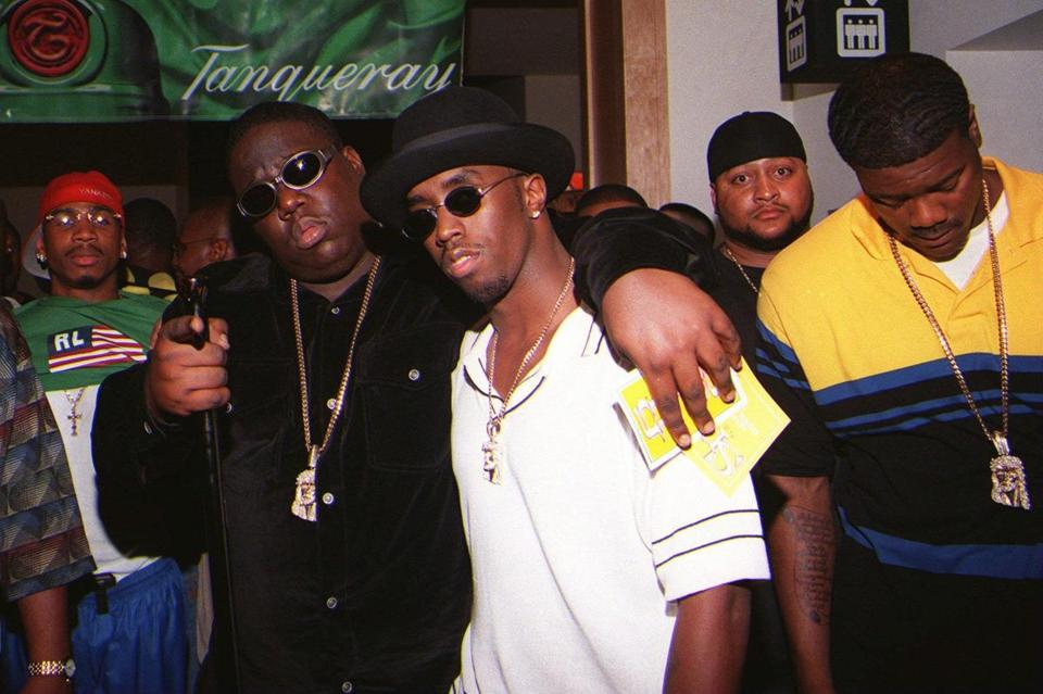 EDS NOTE: NO SALES -- Notorious B.I.G., whose real name is Christopher Wallace, left, gestures as he and producer Sean 'Puffy' Combs leave a party at the Petersen Automotive Museum in Los Angeles late Saturday evening, March 8, 1997, shortly before Wallace was shot to death. The men on the far right and left are unidentified but are thought to be the rapper's bodyguards. (AP Photo/Venus Bernardo-Prudhomme)