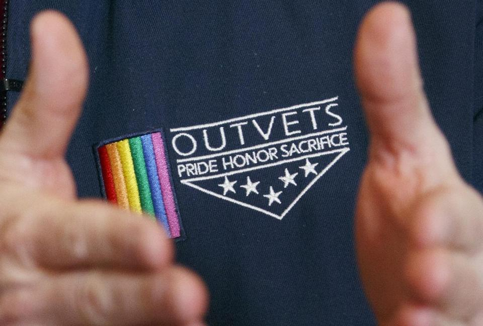 OutVets founder Bryan Bishop wore the logo of his group while speaking to reporters Friday.