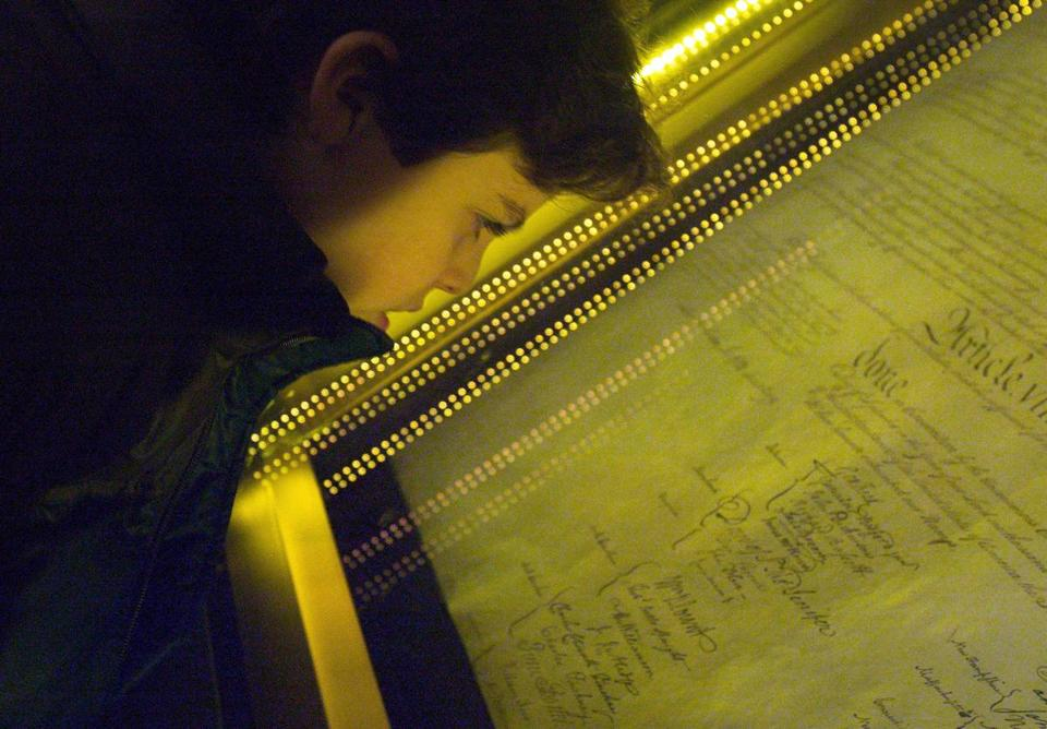 Ethan Kasnett, an 8th grade student at the Lab School in Washington, DC, views the original constitution after a ceremony unveiling the people's choice of the top ten most influential documents that shaped the United States of America at the National Archives December 15, 2003 in Washington, DC. The event and vote were co-sponsored by The People's Vote, the National Archives and Records Administration, National History Day, and U.S. News & World Report. Among the records chosen were the Declaration of Independence at number one and the Constitution at number two. (Photo by Brendan Smialowski/Getty Images) Restrictions