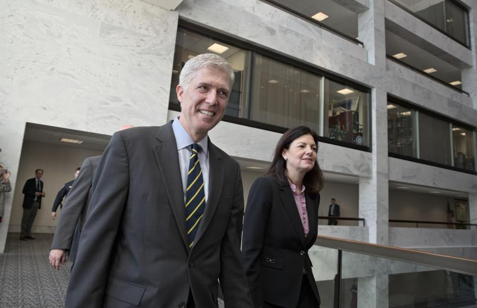FILE - In this Feb. 6, 2017 file photo, Supreme Court Justice nominee Neil Gorsuch, escorted by former New Hampshire Sen. Kelly Ayotte, arrives for meeting on Capitol Hill in Washington. The Trump administration's ongoing efforts to implement a travel ban against immigrants from certain countries could easily reach the U.S. Supreme Court. But there's no hint of an eventual outcome if Neil Gorsuch gets on the highest court and casts the deciding vote. (AP Photo/J. Scott Applewhite, File)