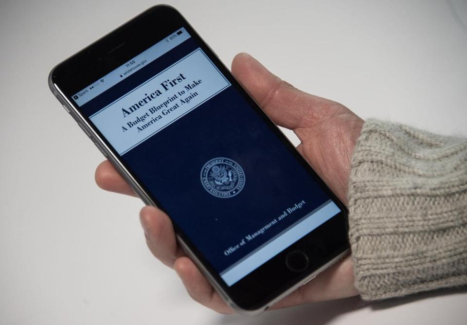 A woman looks at the title page of US President Donald Trump's proposed budget on the White House website on a smartphone in Washington, DC, on March 16, 2017. In a plan designed to translate bold campaign promises into dollar and cent commitments, the Republican leader will propose a 28 percent cut in State Department funding. The Pentagon will be the major winner with a nearly 10 percent boost -- shoveling more cash toward a defense budget already greater than that of the next seven nations combined. / AFP PHOTO / NICHOLAS KAMM (Photo credit should read NICHOLAS KAMM/AFP/Getty Images)