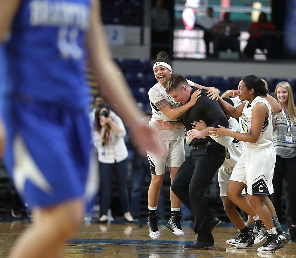 Springfield MA 3/18/17 Springfield Central Golden Eagles Phyness Young Baldwin (left) and Alayah Sweeney jumping on head coach Erik Maurer after they defeated Braintree High Wamps 61-45 during the 2017 MIAA Girls Division 1a State Finals at MassMutual Center. (Photo by Matthew J. Lee/Globe staff) topic: reporter: