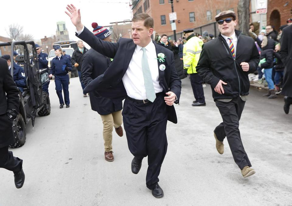 Boston Mayor Martin J. Walsh waved as he ran to catch up with the front of the parade.