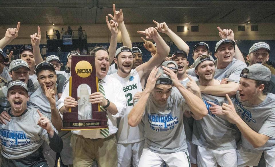 Babson coach Stephen Brennan holds the NCAA Division 3 men's basketball trophy as his players celebrate in Salem, Va. (DON PETERSEN/ASSOCIATED PRESS)