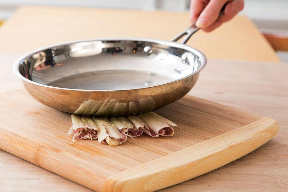 The outer layers of fresh lemon grass are tough and must be removed  to reach the tender core. I use a heavy skillet to bash the lemon grass to  break the outer layers, making it easy to peel them away.
