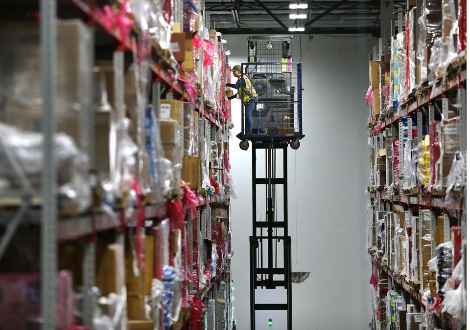 A worker on a lift wearing a safety harness retrieves an item for an order from the top shelf.