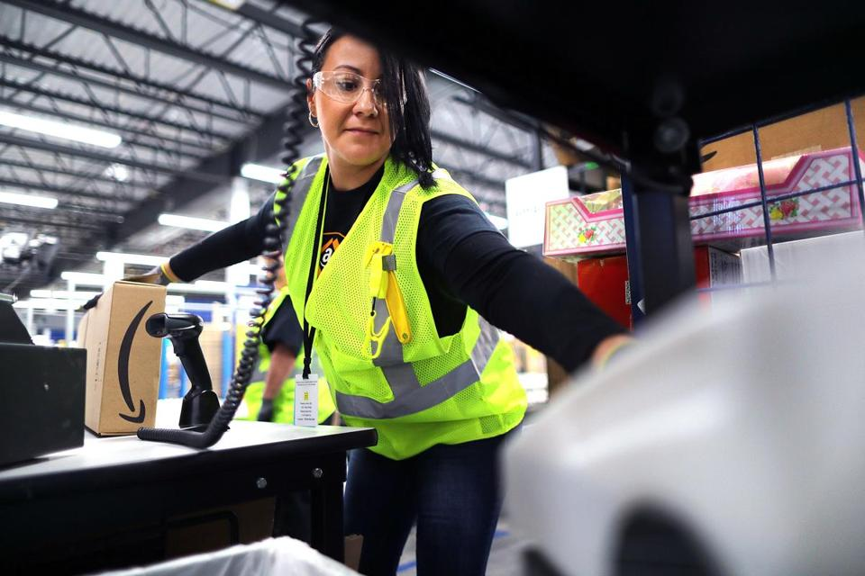 Worker Yesenia Gonzalez reaches for tape to secure a box shut as she processes an order.