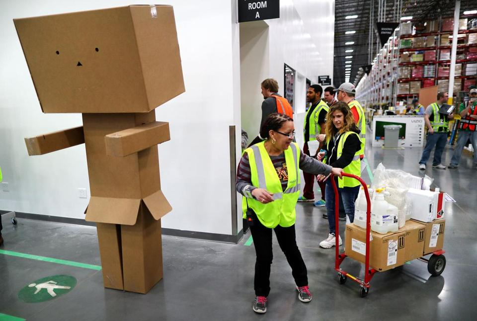 "Workers pass by ""packie"" a box sculpture near the entrance to the warehouse."