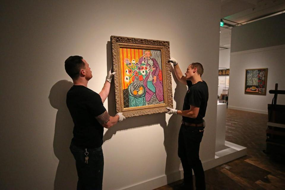 "Sean Cooper (left) and Bob Farrell hang ""Purple Robe and Anemones,"" part of ""Matisse in the Studio,"" which opens April 9 at the MFA."