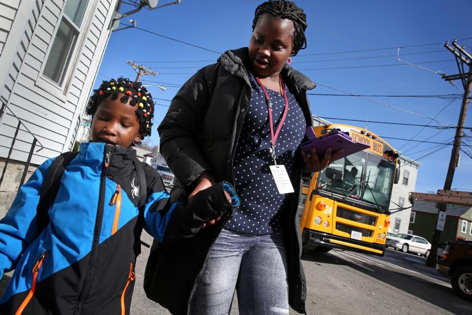 Maria Uwimana, 17, right, walked her sister, Sarah Bayavuge, 7, home from the bus stop after school in Lowell.
