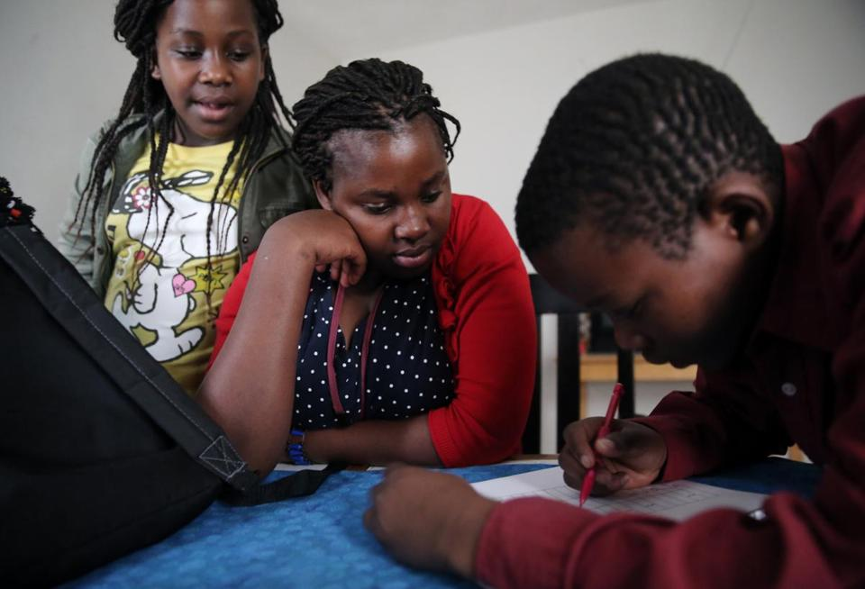 Lea Nyiramahoro, 12, and Maria Uwimana, 17, watched their brother Dusenge Tuyishime, 15, do his schoolwork at their home in Lowell.