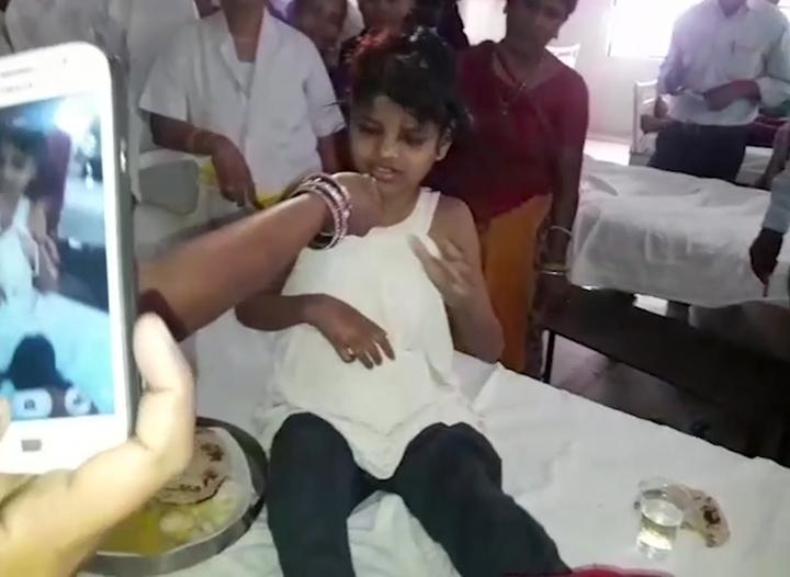 A young Indian girl sat on a bed at a hospital on Thursday.