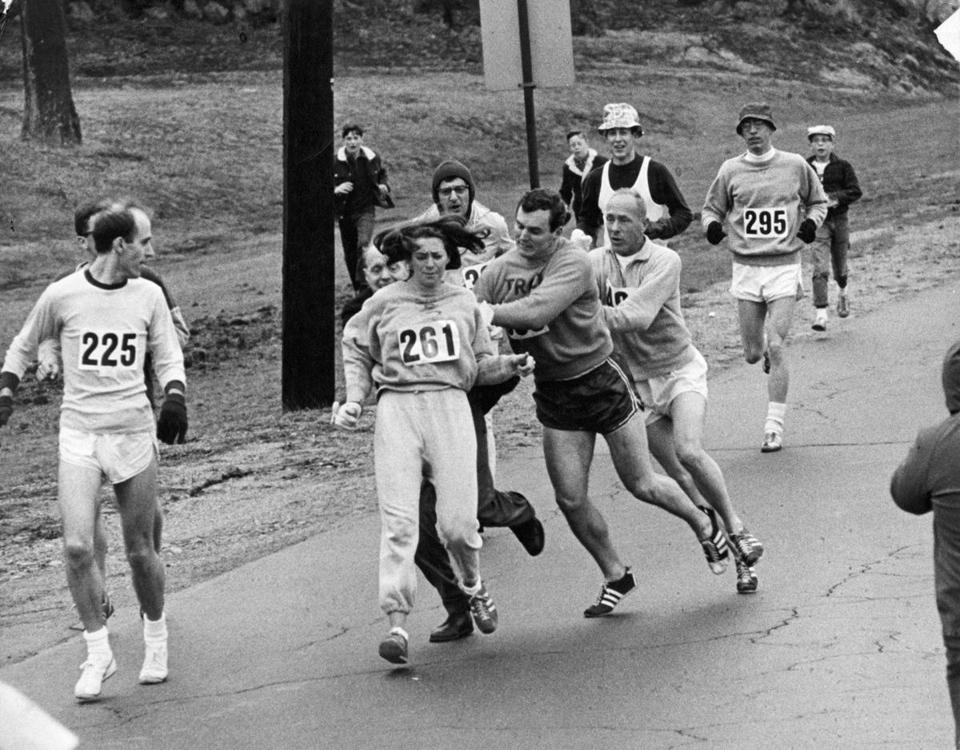 In 1967, Kathrine Switzer, of Syracuse, N.Y., center, was spotted early in the Boston Marathon by Jock Semple, center right, who tried to rip the number off her shirt and remove her from the race.