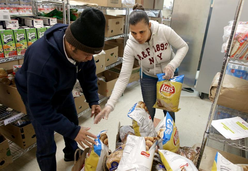Volunteer Paillant Bod (left) and Jacelys de Pena pack groceries at the Catholic Charities Archdiocese of Boston Yawkey Center food pantry in Dorchester.