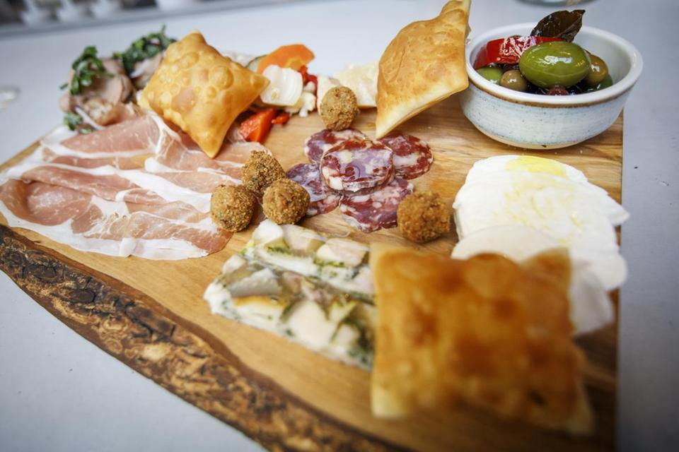 Boston, MA - 4/10/2017 - The chef's selection board with prosciutto di toscana, pate del cacciatore, porches di testa, olives, giardiniera, gnocchi fret, frittelle di prosciutto, buffalo mozzarella, and parmagiano reggiano with honey sits on a table at Eataly's restaurant Terra in Boston, MA, April 10, 2017. (Keith Bedford/Globe Staff)