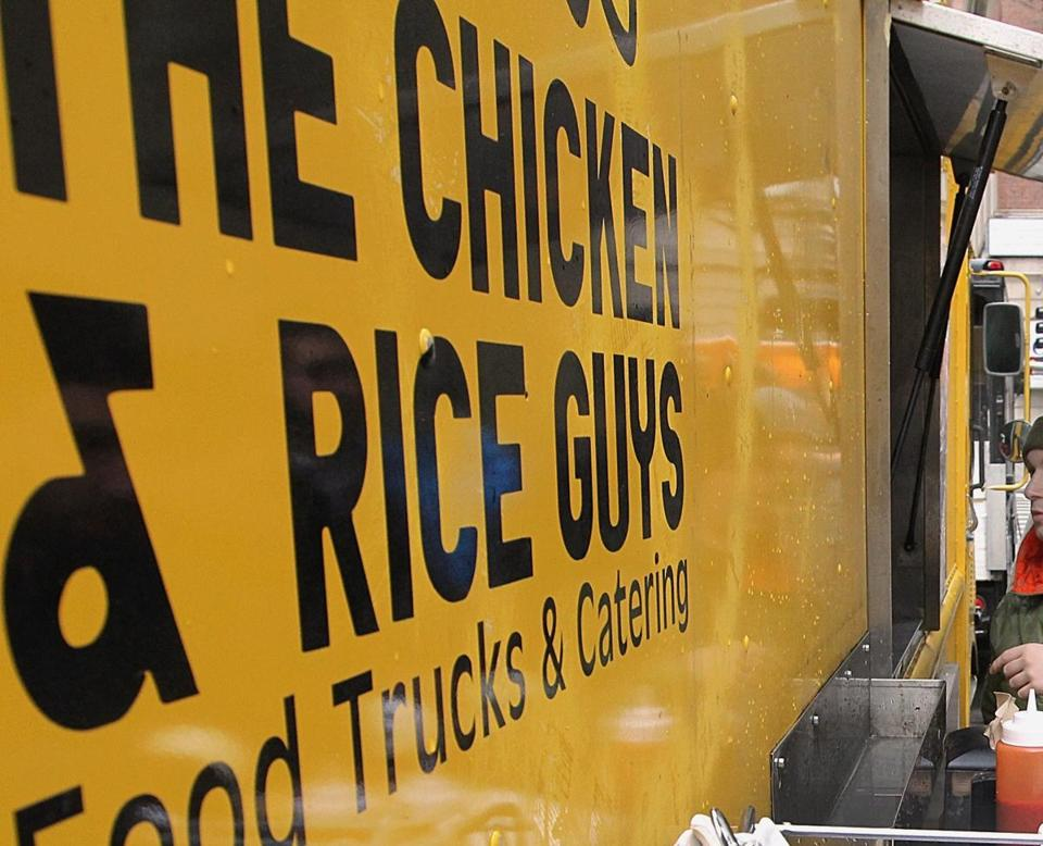 Boston, MA 121714 (ltor) Fiksu employees Max Weinstein (cq) and Phil Wu (cq) are regulars at the Chicken and Rice Guys food truck at Copley Square, Wednesday, December 17 2014. (Wendy Maeda/Globe Staff) section: Business slug: xxBusinessLunch-Johnston01 reporter: Katie Johnston
