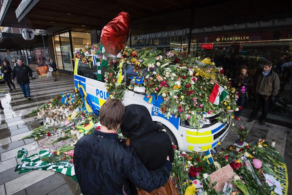 A couple hugged in front of a flower-covered police car at the site of last week's attack.