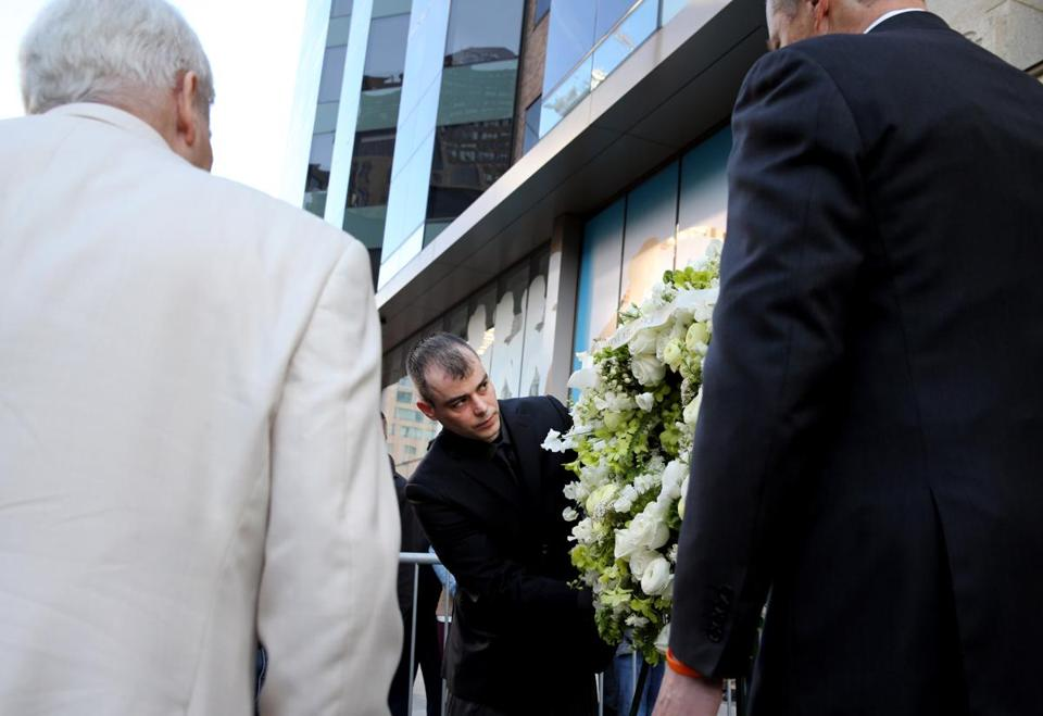 "Boston, MA- April 15, 2017: William Campbell III, center, brother of Boston Marathon bombing victim, Krystle Campbell, is flanked by his father William Campbell Jr. left, and Governor Charles ""Charlie"" Baker, right, during the One Boston Day wreath laying on Boylston St. in Boston, MA, on April 15, 2017. This ceremony took place outside Marathon Sports, the site of the first explosion on April 15, 2013. (Globe staff photo / Craig F. Walker) section: metro reporter ( I understand another ceremony took place at the site of the second ceremony at the same time)"